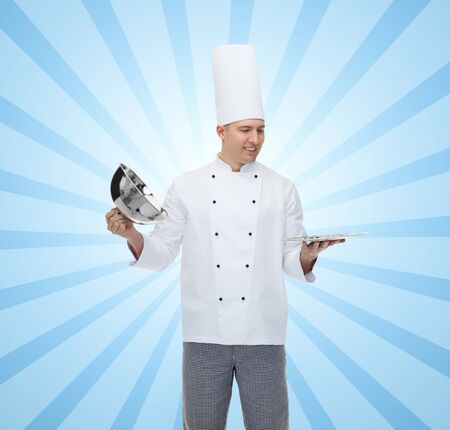 cloche: cooking, profession and people concept - happy male chef cook opening cloche cover over blue burst rays background