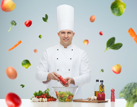 profession, vegetarian, food and people concept - happy male chef cooking and seasoning vegetable salad over gray background Stock Photo