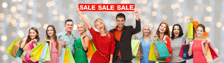 consumerism, people and discount concept - group of happy people with sale sign and shopping bags over holidays lights background Stockfoto