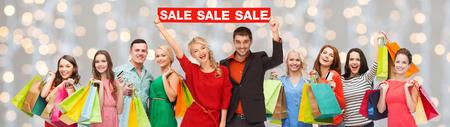 consumentisme, mensen en korting concept - groep van gelukkige mensen met verkoop ondertekenen en boodschappentassen over vakantie steekt achtergrond aan Stockfoto