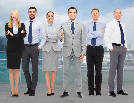 negocio, la gente, el gesto y el concepto de Oficina - grupo de sonrientes empresarios hacer apretón de manos sobre fondo de la ciudad Foto de archivo