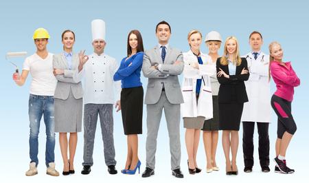 人、専門職、資格、雇用および成功コンセプト - 青い背景の上の専門の労働者のグループで幸せなビジネスマン
