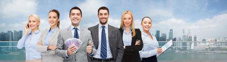 eur: business, people and finances concept - group of smiling businessman with american dollar money Stock Photo