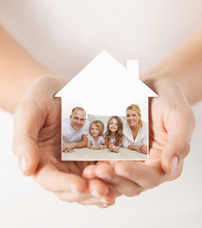 hands holding house: real estate, home insurance and happiness concept - close up of female hands holding white house with happy family picture