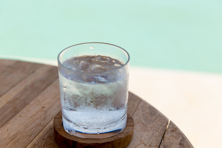 water concept: travel, tourism, drinks and refreshment concept - glass of cold water with ice cubes on table at beach