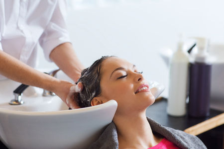 lavandose las manos: la belleza y el concepto de la gente - mujer joven feliz con la cabeza de lavado peluquero en el sal�n de pelo