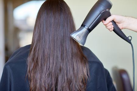 beauté, soins capillaires, brushing, coiffure et les gens concept - styliste main avec ventilateur sèche cheveux femme au salon