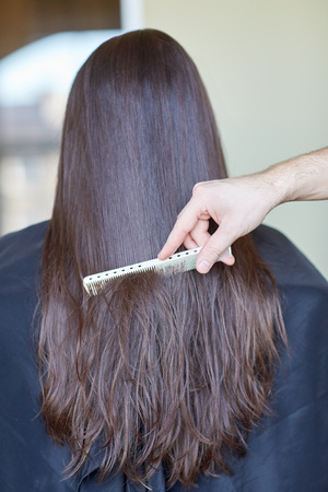 hair stylist: beauty, hair care, hairstyle and people concept - stylist hand with comb combing woman hair at salon