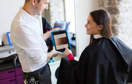showing: beauty, technology and people concept - happy young woman and stylist with tablet pc computer choosing hair color at salon