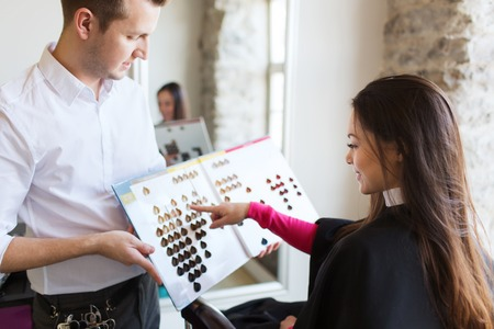 beauty, hair dyeing and people concept - happy young woman with hairdresser choosing hair color from palette samples at salon Standard-Bild