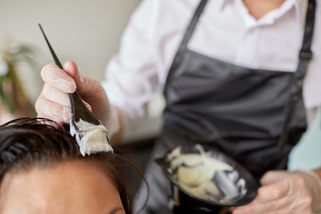 beauty and people concept - close up of stylist with hair dye and brush coloring hair at salon
