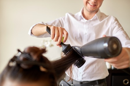 beauty, hairstyle, blow-dry and people concept - close up of woman and hairdresser with fan and brush making hot styling at hair salon