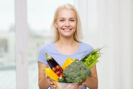 eating food: healthy eating, vegetarian food, dieting and people concept - smiling young woman with bowl of vegetables at home