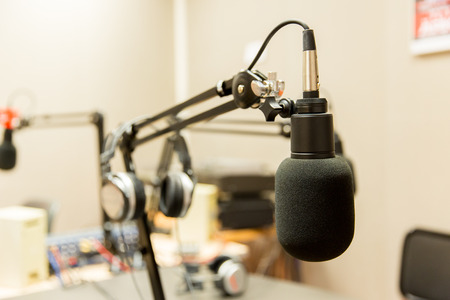 Radio: technology, electronics and audio equipment concept - close up of microphone at recording studio or radio station