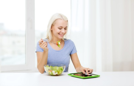 health technology: healthy eating, dieting and people concept - smiling young woman with tablet pc computer eating vegetable salad at home Stock Photo