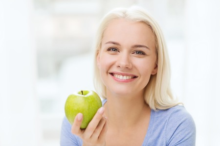 eating food: healthy eating, organic food, fruits, diet and people concept - happy woman eating green apple at home