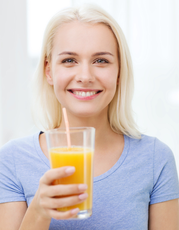 orange juice: healthy eating, vegetarian food, diet, detox and people concept - smiling woman drinking orange juice or shake from glass at home