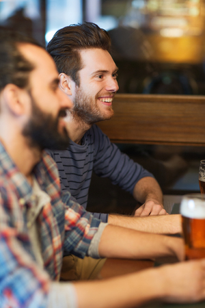 happy customer: people, men, leisure, friendship and communication concept - happy male friends drinking beer at bar or pub