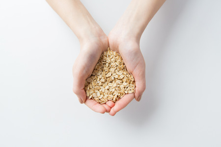 cereals holding hands: healthy eating, dieting, vegetarian food and people concept - close up of woman hands holding oatmeal flakes at home Stock Photo