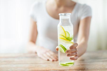 tomando agua: alimentación saludable, las bebidas, la dieta, la desintoxicación y el concepto de personas - cerca de la mujer con el agua de fruta en botella de vidrio