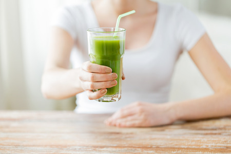 healthy eating, food, diet, detox and people concept - close up of woman hands with green juice on wooden table