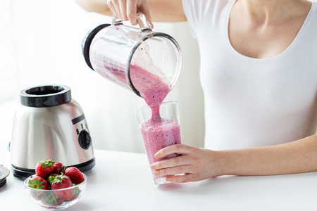healthy eating, cooking, vegetarian food, dieting and people concept - close up of woman with blender and strawberries pouring milk shake to glass at home