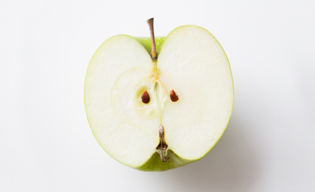 fruits, diet, eco food and objects concept - ripe green apple half over white