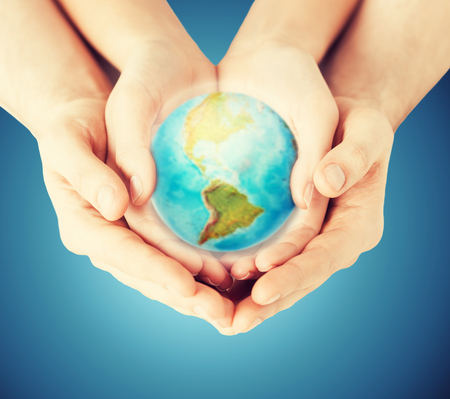 population: people, geography, population and peace concept - close up of woman and man hands with earth globe showing american continent over blue background Stock Photo