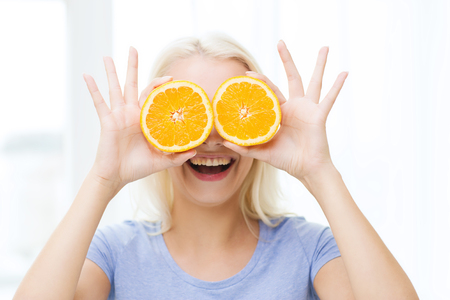 nutrients: healthy eating, organic food, fruit diet, comic and people concept - happy woman having fun and covering her eyes with orange slices Stock Photo
