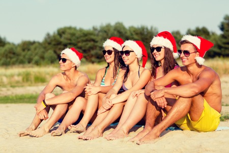 headwear: friendship, happiness, summer vacation, holidays and people concept - group of friends in santa helper hats sitting on beach