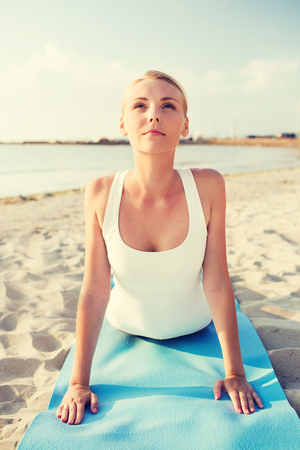 beach mat: fitness, sport, people and lifestyle concept - young woman making yoga exercises lying mat outdoors
