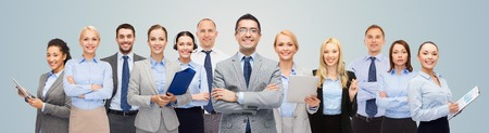 american banker: business, people, corporate, teamwork and office concept - group of happy businesspeople over blue background Stock Photo