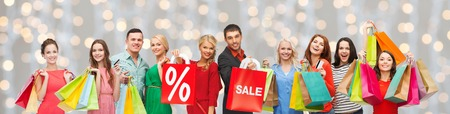 consumerism: consumerism, people and discount concept - group of happy people with percentage and sale sign on shopping bags over holidays lights background