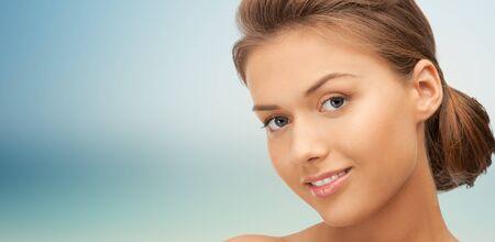 la beauté, les gens et le concept de santé - belle jeune visage de femme sur fond bleu
