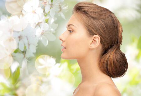 visage profil: la santé, les gens, éco et le concept de la beauté - belle jeune visage de femme sur fond vert floraison de jardin