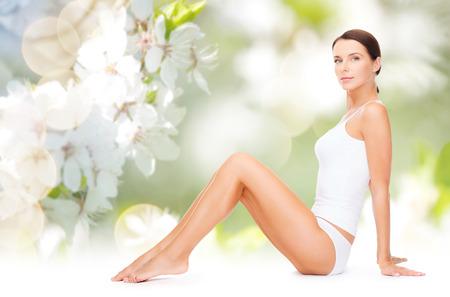 conceito de cuidados de pessoas, beleza e corpo - mulher bonita em roupa íntima de algodão, mostrando as pernas sobre fundo verde natural flor de cerejeira