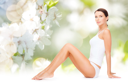 depilation: people, beauty and body care concept - beautiful woman in cotton underwear showing her legs over green natural cherry blossom background