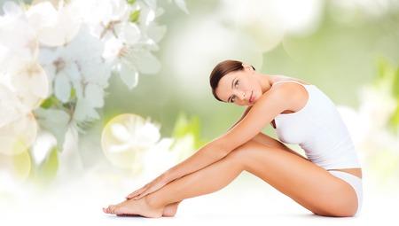 Menschen, Schönheit und Körperpflege-Konzept - schöne Frau in Unterwäsche aus Baumwolle zu berühren Beine über grüne natürlichen Kirschblüte Hintergrund