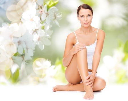 cuerpo perfecto femenino: la gente, la belleza y el cuidado del cuerpo concepto - hermosa mujer en ropa interior de algodón piernas tocando sobre fondo verde flor de cerezo natural Foto de archivo