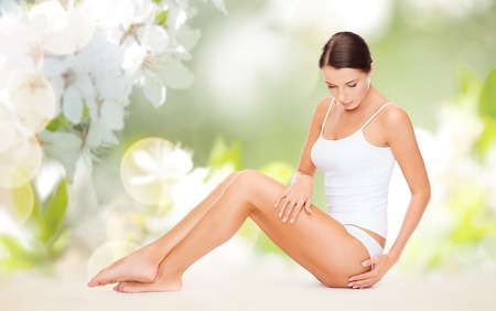 'fit body': people, beauty and body care concept - beautiful woman in cotton underwear touching her hips over green natural cherry blossom background