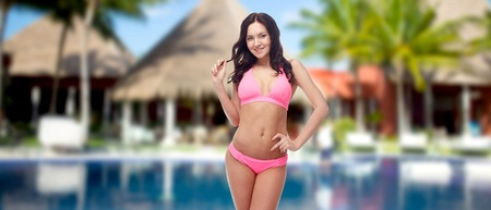 people, fashion, summer vacation and travel concept - happy young woman posing in pink bikini swimsuit over hotel resort with swimming pool, bungalow and palm trees background