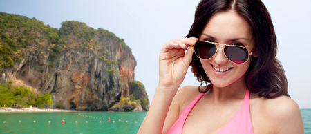 you: people, fashion, summer accessories and beach concept - happy young woman in sunglasses and pink swimsuit looking at you over sea and rock background Stock Photo