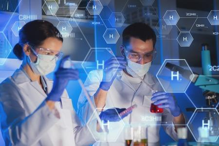 la ciencia, la química, la biología, la medicina y la gente concepto - Cierre de jóvenes científicos con pipeta y frascos haciendo pruebas o la investigación en laboratorio clínico sobre la fórmula química de hidrógeno Foto de archivo