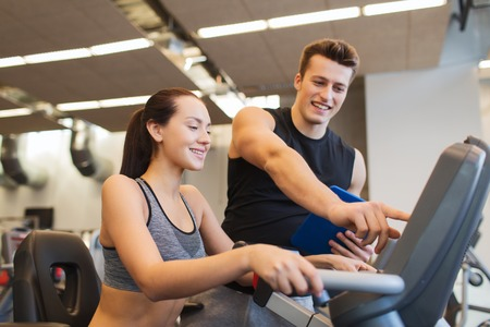 fitness gym: sport, fitness, lifestyle, technology and people concept - happy woman with trainer working out on exercise bike in gym Stock Photo