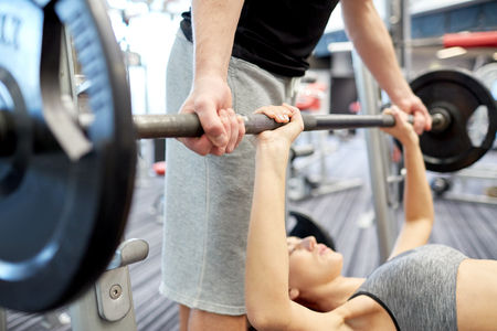 lifting: sport, fitness, teamwork, weightlifting and people concept - close up of young woman and personal trainer with barbell flexing muscles in gym