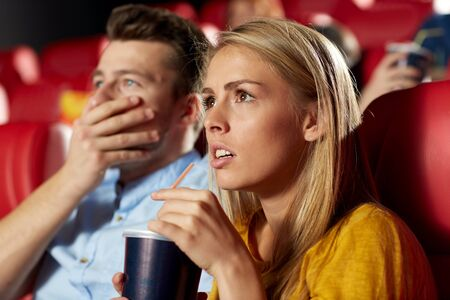 thriller: cinema, entertainment and people concept - couple drinking soda and watching horror, drama or thriller movie in theater