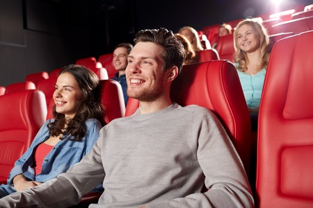 theater seat: cinema, entertainment and people concept - happy friends watching movie in theater