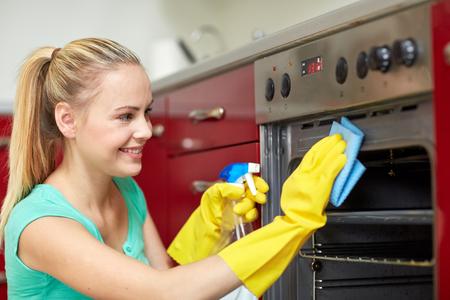 orden y limpieza: las personas, el trabajo doméstico y el concepto de servicio de limpieza - mujer feliz con la botella de horno de limpieza de limpieza en aerosol en la cocina de casa