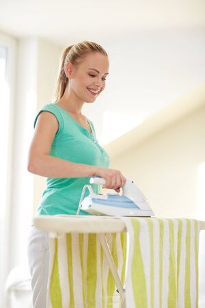 mensen, huishoudelijk werk, wasserette en housekeeping concept - gelukkige vrouw met strijkijzer en strijkplank thuis