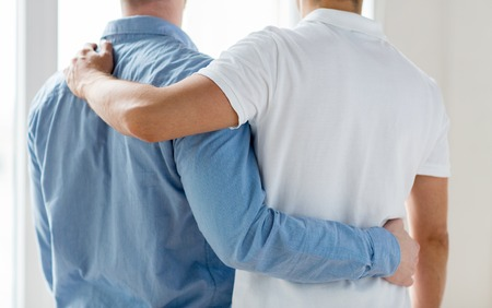 same sex: people, homosexuality, same-sex marriage, gay and love concept - close up of happy male gay couple or friends hugging from back Stock Photo
